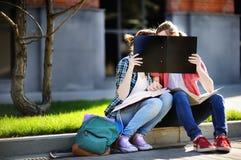 亲吻和握手的年轻愉快的学生 图库摄影