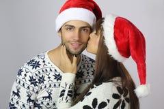 亲吻圣诞老人帽子的妇女英俊的人 图库摄影