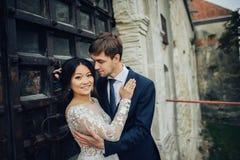 亲吻在与城堡墙壁bac的日落的新婚佳偶愉快的夫妇  免版税图库摄影