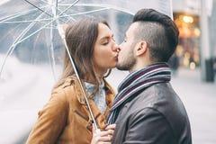亲吻在伞下的年轻夫妇在下雨天在市中心-有浪漫的恋人室外嫩的片刻 免版税库存图片