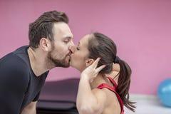 亲吻在健身房的年轻夫妇 库存图片