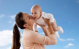 亲吻在天空的愉快的母亲小男婴 免版税库存图片