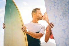 亲吻在拿着冲浪板-愉快的恋人的海滩的日落的冲浪者健康年轻夫妇有与亲吻的嫩片刻 免版税库存照片