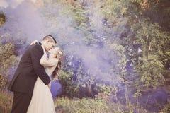 亲吻在有紫色烟的森林里的新娘和新郎 免版税库存图片