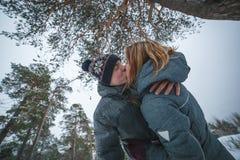 亲吻在杉树下的愉快的年轻美好的夫妇在多雪的冬天森林里 免版税库存图片