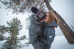 亲吻在杉树下的愉快的年轻美好的夫妇在多雪的冬天森林里 免版税图库摄影