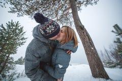 亲吻在杉树下的愉快的年轻美好的夫妇在多雪的冬天森林里 免版税库存照片