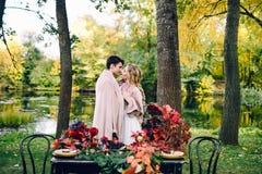 亲吻在格子花呢披肩下的新婚佳偶在欢乐桌旁边 新娘和新郎在公园 秋天婚礼 附庸风雅 免版税图库摄影