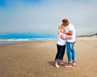 亲吻在海滩的新夫妇 免版税库存图片