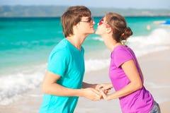 亲吻在热带海滩的新愉快的夫妇。   免版税库存图片