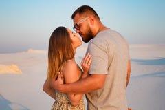 亲吻在白色沙子海滩或在沙漠或在沙丘,愉快的夫妇的可爱的有吸引力的夫妇拥抱在beac 图库摄影
