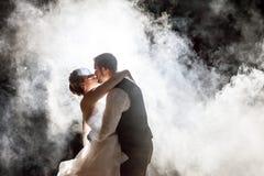 亲吻在雾的新娘和新郎在晚上 免版税库存图片