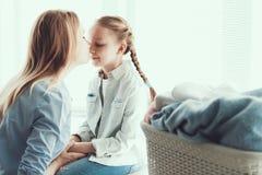 亲吻在鼻子的年轻愉快的母亲一点Daugther 库存图片