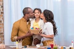亲吻女儿和拿着秸杆篮子用复活节彩蛋的父母 免版税库存照片
