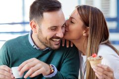 亲吻她的丈夫或男朋友面颊的愉快的年轻女人 在咖啡馆的浪漫日期 免版税库存照片
