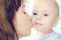 亲吻她的儿童女孩的美丽的母亲画象 免版税库存照片