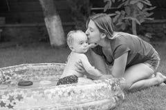 亲吻她的在可膨胀的游泳池的愉快的年轻母亲黑白照片婴孩游泳 库存照片