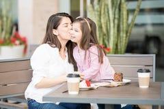 亲吻她的女儿的母亲在餐馆 库存图片
