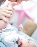 亲吻她的婴孩的英尺的母亲 免版税库存图片