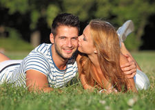 亲吻她的朋友的愉快的女朋友室外 库存照片