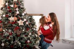 亲吻她的母亲的愉快的孩子在冷杉木附近 免版税库存图片
