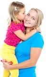 亲吻她的母亲的时兴的小孩 图库摄影