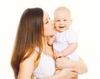 亲吻她的白色背景的愉快的母亲婴孩 免版税库存图片
