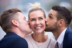 亲吻她的面颊的两个年轻人妇女 免版税库存照片