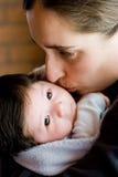 亲吻妈咪的婴孩 库存照片