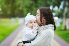 亲吻婴孩的妈妈特写镜头画象户外在公园背景 免版税图库摄影
