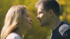 亲吻年轻的夫妇,与秋天叶子,浪漫日期,特写镜头的人掩藏的面孔 影视素材