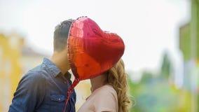 亲吻愉快的夫妇,掩藏在心脏气球后,浪漫关系,日期 免版税库存图片