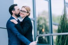 亲吻成熟的商业的人拥抱和,当站立外面时 库存照片