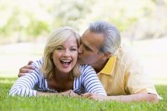亲吻户外公园的夫妇放松 免版税库存照片