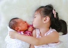亲吻新生儿的可爱的亚裔姐妹说谎在白色毛皮背景 免版税图库摄影