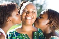 亲吻母亲的女儿 免版税库存照片