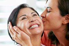 亲吻母亲的成人女儿纵向 免版税库存照片