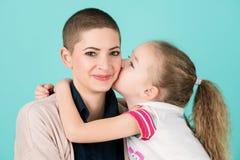 亲吻母亲,年轻癌症患者的女孩,面颊的 巨蟹星座和家庭支持 免版税库存照片