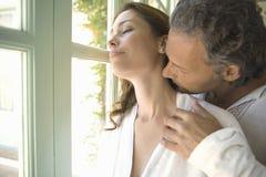 亲吻由庭院门的成熟夫妇。 免版税库存照片