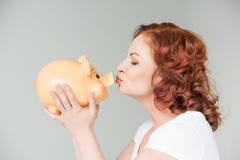 亲吻贪心妇女的银行 库存照片