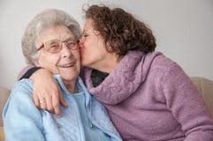 亲吻资深妇女的年轻女人 免版税库存照片