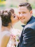 亲吻面颊的新娘的特写镜头画象新郎 免版税图库摄影