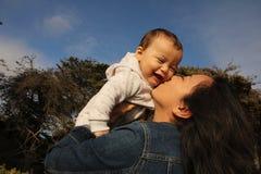 亲吻面颊的母亲孩子 免版税库存图片
