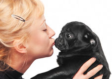 亲吻黑色哈巴狗小狗的逗人喜爱的金发碧眼的女人 库存照片