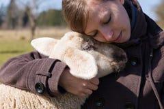 亲密地拥抱一只小的羊羔的俏丽的妇女 免版税图库摄影
