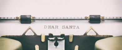 亲爱的圣诞老人用大写字母在打字机板料 免版税库存照片