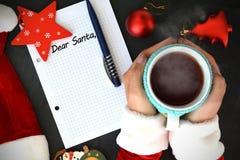 亲爱的圣诞老人,在算术书的文本用拿着一个杯子用热的茶的妇女手在Santa's帽子和圣诞节辅助部件附近 免版税库存照片