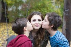 亲吻一个十几岁的女孩的两个男孩 库存图片