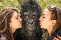 亲吻一个吃惊的大猩猩的两个女孩 库存图片