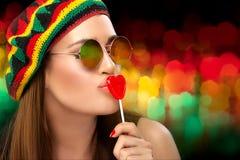 亲吻一个心形的棒棒糖的时髦的女招待 免版税图库摄影